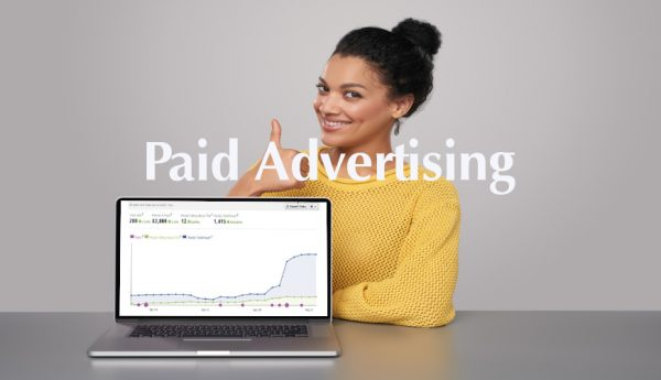 Happy mixed race african american - caucasian woman showing blank black laptop computer screen, looking at camera smiling, gesturing thumb up while showing her increased book sales graph on her laptop
