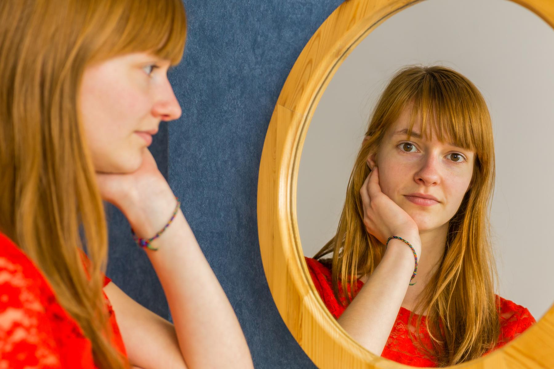 Caucasian redhead teenage girl looking in mirror