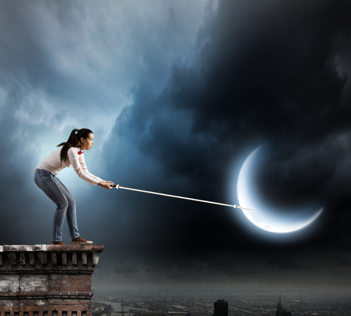 young woman standing on the top of a brick building with a long hook appearing to pull the moon toward herlong hoo