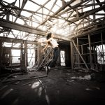 Woman jumping forward in a building that appears to be falling apart