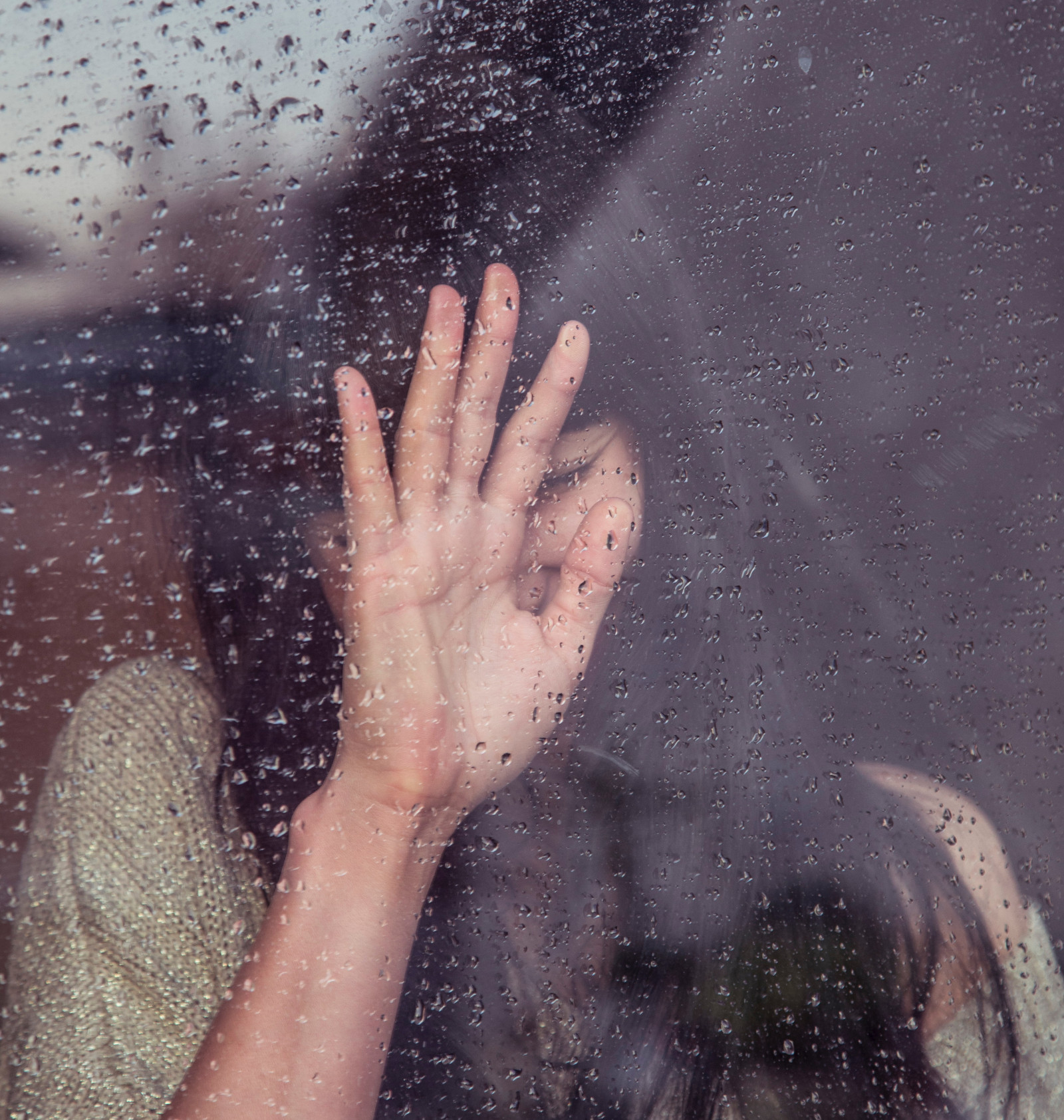 woman in shadow with her hand against a pane of glass with rain on it