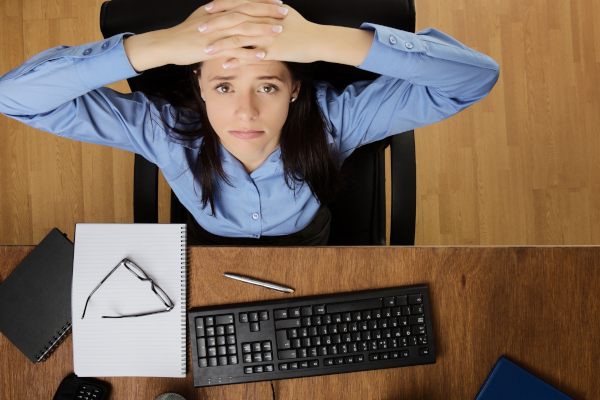 woman at her desk feeling the stress of work, taken from a birds eye view