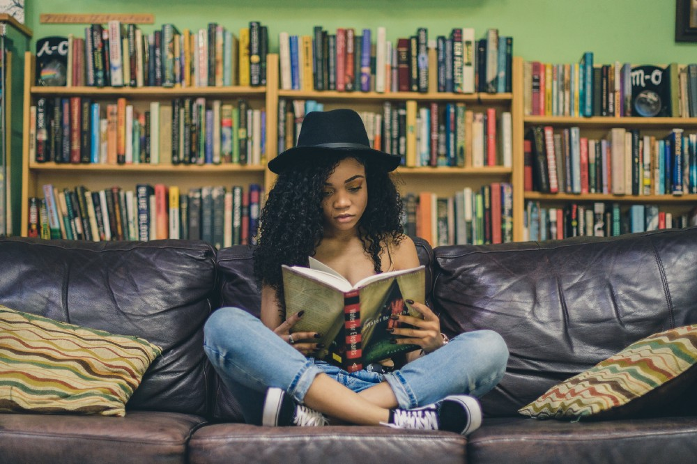 african american woman reading on a sofa in front of a large library of books behind her