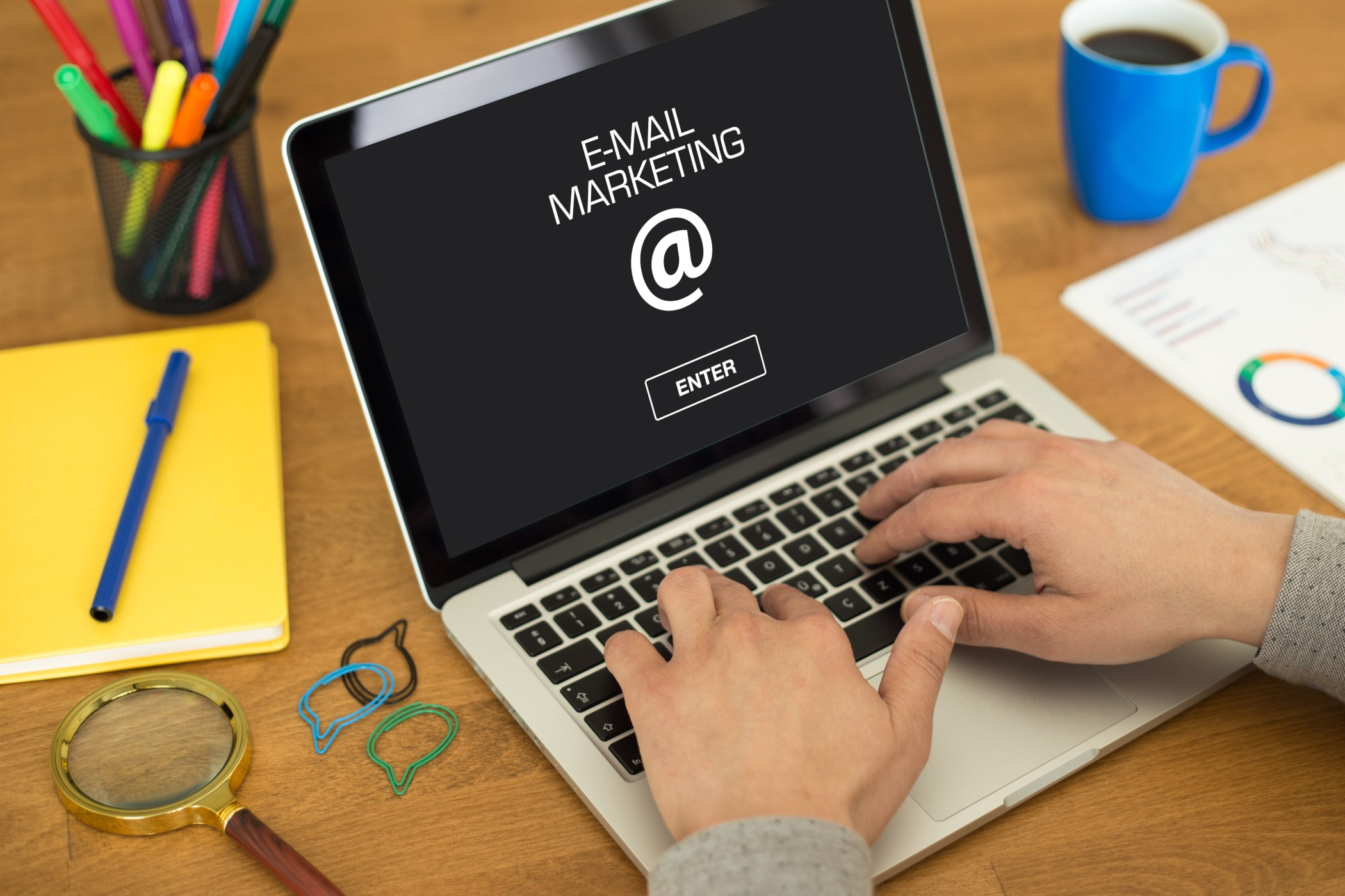 """picture of hands on keyboad of laptop with the words """"email marketing"""" displayed and the @ sign"""