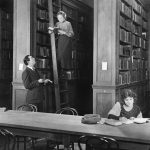 old-fashioned library with woman on a ladder reading a ook, a man below her asking a quesiton, and another woman at a table reading a ook